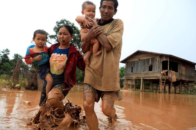 Parents in Laos evacuating flood caused by dam collapse